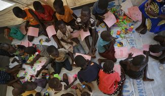 """FILE - In this Friday, June 9, 2017 file photo, unaccompanied or separated children play and draw on the floor of a World Vision tent as they wait for child protection specialists to evaluate their situations at the Imvepi reception center, where newly arrived refugees are processed before being allocated plots of land in nearby Bidi Bidi refugee settlement, in northern Uganda. The latest report on human rights abuses in South Sudan's five-year civil war, released by a United Nations commission Friday, Feb. 23, 2018 says it has identified more than 40 senior military officials """"who may bear individual responsibility for war crimes."""" (AP Photo/Ben Curtis, File)"""