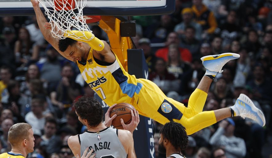 Denver Nuggets guard Jamal Murray, back, hangs from the rim after dunking over San Antonio Spurs center Pau Gasol during the second half of an NBA basketball game Friday, Feb. 23, 2018, in Denver. The Nuggets won 122-119. (AP Photo/David Zalubowski)