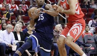 Minnesota Timberwolves guard Jimmy Butler (23) drives around Houston Rockets forward Ryan Anderson (33) during the first half of an NBA basketball game Friday, Feb. 23, 2018, in Houston. (AP Photo/Michael Wyke)
