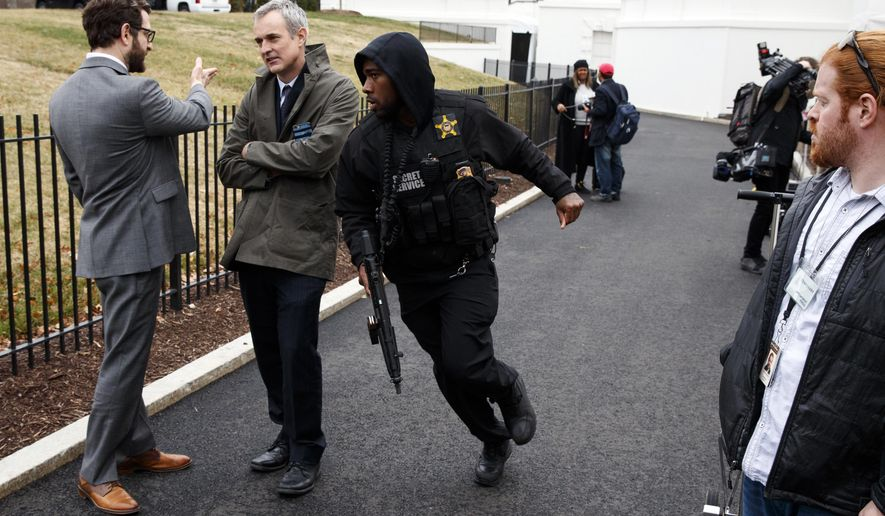 A Secret Service officer rushes past reporters after a vehicle rammed into a security barrier near the White House, Friday, Feb. 23, 2018, in Washington. (AP Photo/Evan Vucci)