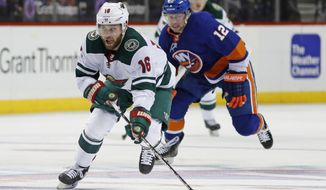 Minnesota Wild left wing Jason Zucker (16) skates with the puck as New York Islanders right wing Josh Bailey (12) pursues him during the third period of an NHL hockey game in New York, Monday, Feb. 19, 2018. The Wild defeated the Islanders 5-3. (AP Photo/Kathy Willens)