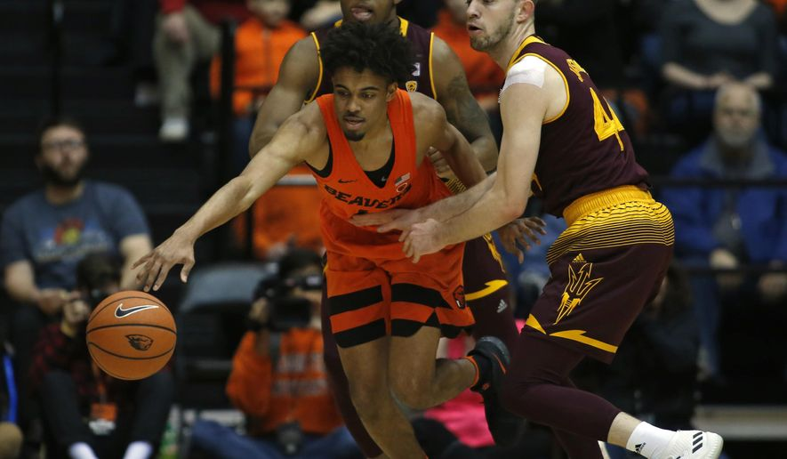 Oregon State's Stephen Thompson Jr., center, protects the ball from Arizona State's Kimani Lawrence, rear, and Kodi Justice, right, in the first half of an NCAA college basketball game in Corvallis, Ore., Saturday, Feb. 24, 2018. (AP Photo/Timothy J. Gonzalez)