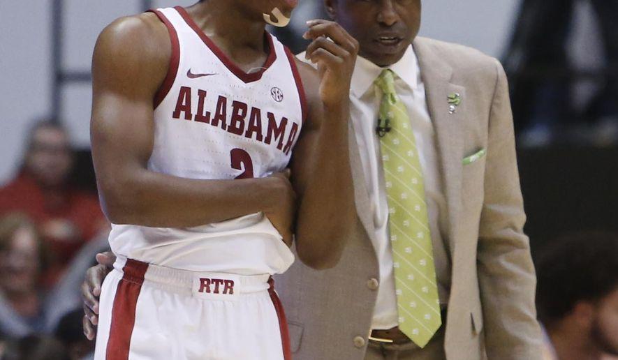 Alabama coach Avery Johnson talks to guard Collin Sexton (2) in the first half of the team's NCAA college basketball game against Arkansas in Tuscaloosa, Ala., Saturday, Feb. 24, 2018. (Erin Nelson/The Tuscaloosa News via AP)