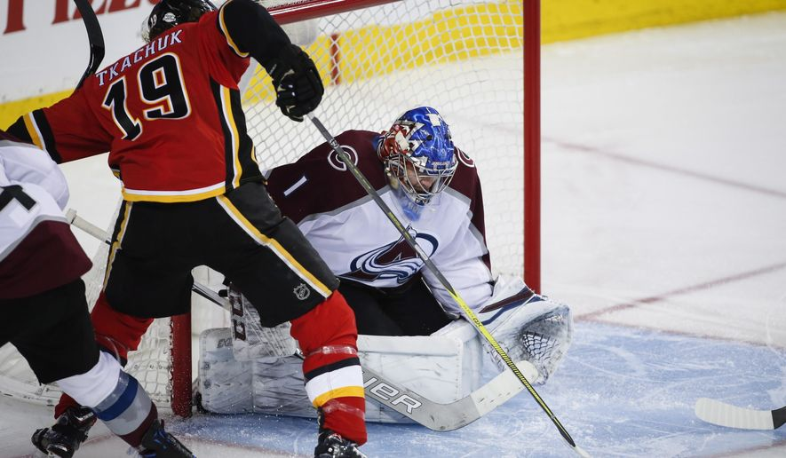 Colorado Avalanche goalie Semyon Varlamov, right, of Russia, blocks the net on Calgary Flames' Matthew Tkachuk during third-period NHL hockey game action in Calgary, Alberta, Saturday, Feb. 24, 2018. (Jeff McIntosh/The Canadian Press via AP)
