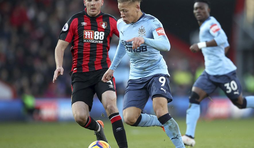 Bournemouth's Dan Gosling, left, and Newcastle United's Dwight Gayle vie for the ball during their Premier League soccer match, Bournemouth against Newcastle United, at the Vitality Stadium, in Bournemouth, England, Saturday, Feb. 24, 2018. (Adam Davy/PA via AP)