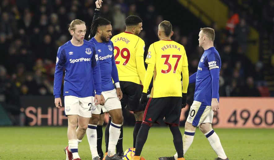 Watford's Etienne Capoue, centre left, receives a yellow card from referee Anthony Taylor during their English Premier League soccer match against Everton, with Wayne Rooney right, at Vicarage Road in London, Saturday Feb. 24, 2018. (Jonathan Brady/PA via AP)