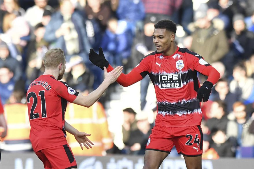 Huddersfield Town's Steve Mounie, right, celebrates scoring his side's second goal of the game during the English Premier League soccer match, West Bromwich Albion against Huddersfield Town at The Hawthorns, West Bromwich, England, Saturday Feb. 24, 2018. (Anthony Devlin/PA via AP)