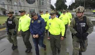 FILE - This undated photo released by Colombia's National Police show officers escorting a man who police identify as Ecuadorean drug trafficker Washington Edison Prado after his April 2017 arrest on an indictment by a Florida federal court. Colombia's chief prosecutor's office said Saturday, Feb. 24. 2018, that it has extradited Prado to the United States. (Colombia National Police via AP, File)
