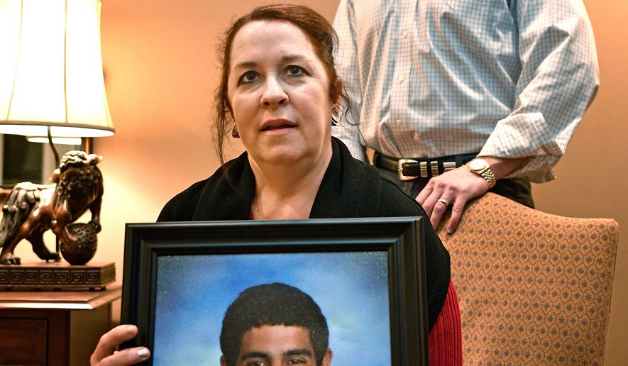 Liz Beatty and her husband Yarnell pose with a photo of their son Alex Tuesday Feb. 13, 2018, in Brentwood, Tenn.. The Beatty's son, Alex, died from an accidental drug overdose in 2016. Since he died, they've been inspired to create a greater dialogue in Williamson County about substance abuse and addiction in young people.  (Larry McCormack/The Tennessean via AP)