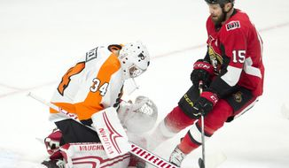 Ottawa Senators left wing Zack Smith pressures Philadelphia Flyers goaltender Petr Mrazek as he tries to control a shot during first period NHL action Saturday, Feb. 24, 2018 in Ottawa. (Adrian Wyld/The Canadian Press via AP)