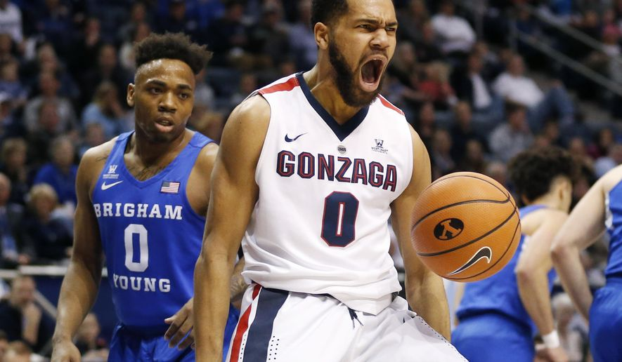 Gonzaga guard Silas Melson (0) reacts after dunking the ball while BYU guard Jahshire Hardnett (0) looks on in the first half of an NCAA college basketball game Saturday, Feb. 24, 2018, in Provo, Utah. (AP Photo/Rick Bowmer)