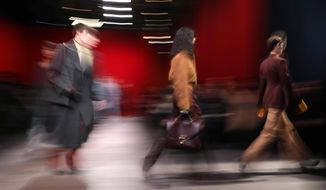 In this photo taken with a slow shutter speed models wear creations  part of the Salavatore Ferragamo women's Fall/Winter 2018-2019 collection, presented during the Milan Fashion Week, in Milan, Italy, Saturday, Feb. 24, 2018. (Matteo Bazzi/ANSA via AP)