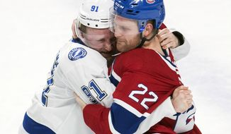 Tampa Bay Lightning center Steven Stamkos (91) fights with Montreal Canadiens defenseman Karl Alzner (22) during first-period NHL hockey game action in Montreal, Saturday, Feb. 24, 2018. (Graham Hughes/The Canadian Press via AP)