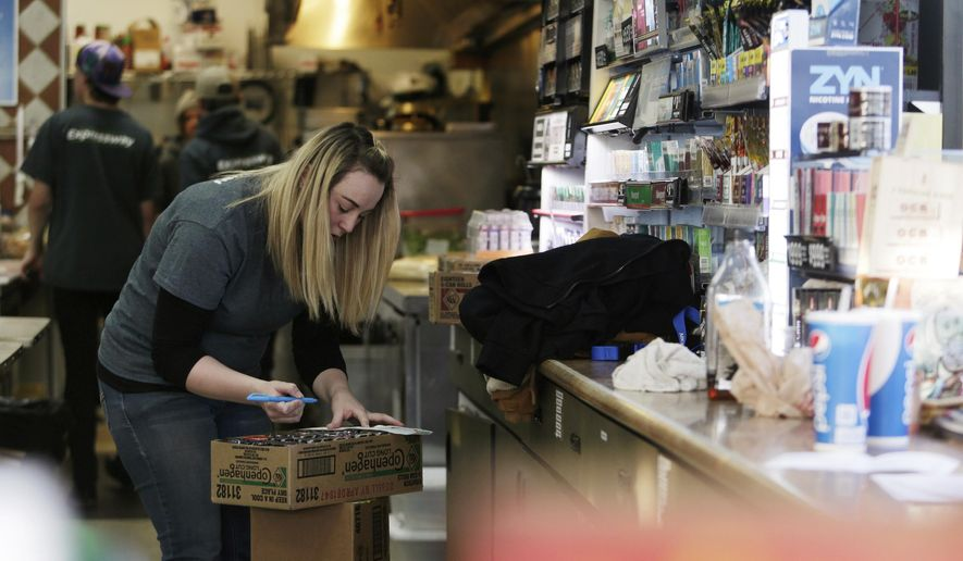 """In this Dec. 13, 2017 photo, Silea Kalebaugh checks over inventory while working at the Expressway in Bend, Ore. Jobs are easy to find in central Oregon these days, but many of them are in low-paying industries. Kalebaugh was recently promoted to night-shift supervisor. """"That job's honestly been a godsend of sorts,"""" Kalebaugh said.  (Joe Kline/The Bulletin via AP)"""