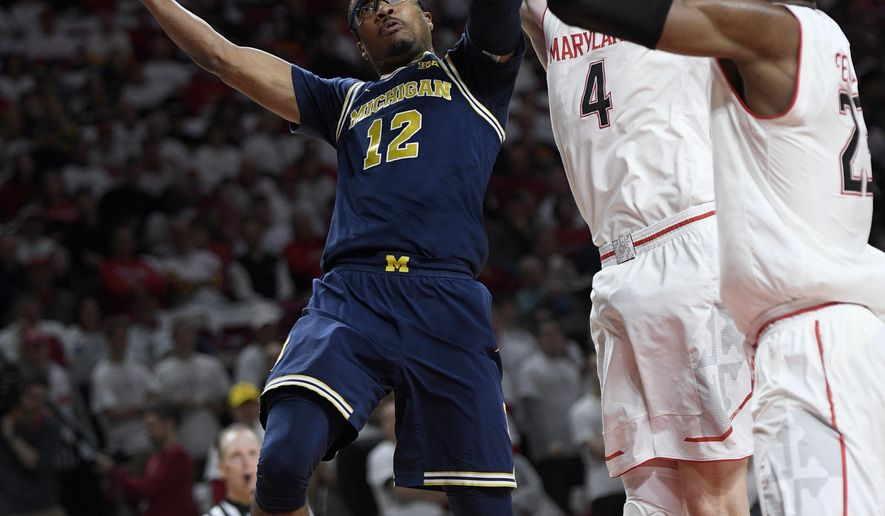 Michigan guard Muhammad-Ali Abdur-Rahkman (12) goes to the basket against Maryland guard Kevin Huerter (4) and forward Bruno Fernando (23) during the first half of an NCAA college basketball game, Saturday, Feb. 24, 2018, in College Park, Md. Huerter was called for a foul on the play.(AP Photo/Nick Wass)