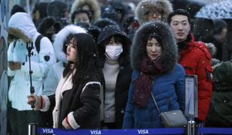 In this Friday, Feb. 23, 2018 photo, people wait in line to enter an Olympic merchandise store at the Pyeongchang Olympic Plaza during the 2018 Winter Olympics in Pyeongchang, South Korea.  The 2018 Winter Olympics may be remembered for many things. The extreme cold during week one. North Koreans participating. Russians here but not under their own flag. And then there is the odd mix of souvenirs and the enormous lines to buy them.  (AP Photo/Charlie Riedel)
