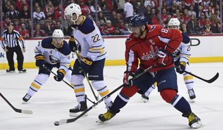 Washington Capitals left wing Alex Ovechkin (8), of Russia, chips the puck past Buffalo Sabres center Johan Larsson (22), defenseman Josh Gorges (4), and center Scott Wilson (20) during the second period of an NHL hockey game in Washington, Saturday, Feb. 24, 2018. (AP Photo/Susan Walsh)
