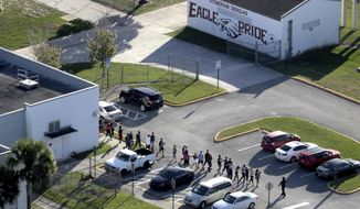 This Feb. 14, 2018, file photo shows students being evacuated by police from Marjory Stoneman Douglas High School in Parkland, Fla., after a former student opened fire on the campus. (Mike Stocker/South Florida Sun-Sentinel via AP, File)