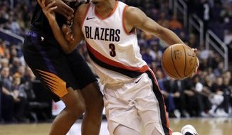 Portland Trail Blazers guard CJ McCollum (3) drives on Phoenix Suns forward TJ Warren during the first half of an NBA basketball game Saturday, Feb. 24, 2018, in Phoenix. (AP Photo/Rick Scuteri)