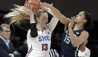 SMU's Klara Bradshaw (13) protects the ball as Connecticut forward Gabby Williams (15) attempts a steal, while UConn coach Geno Auriemma watches during the first half of an NCAA college basketball game Saturday, Feb. 24, 2018, in Dallas. (AP Photo/Tony Gutierrez)