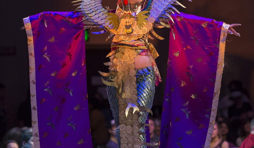 """In this Saturday, Feb. 17, 2018, photo, """"Doragon"""" by artist Beth Bolander is modeled by Dani Gross during the Wearable Art Show at Centennial Hall in Juneau, Alaska. The work of Bolander has been featured in Juneau's annual Wearable Art Show for five years, and her contribution """"Doragon"""" to this year's show sparked a heated discussion about cultural appropriation that led to the piece being removed from Sunday's show. (Michael Penn /The Juneau Empire via AP)"""