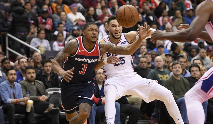 Washington Wizards guard Bradley Beal (3) battles for the ball against Philadelphia 76ers guard Ben Simmons (25) during the second half of an NBA basketball game, Sunday, Feb. 25, 2018, in Washington. The Wizards won 109-94. (AP Photo/Nick Wass)