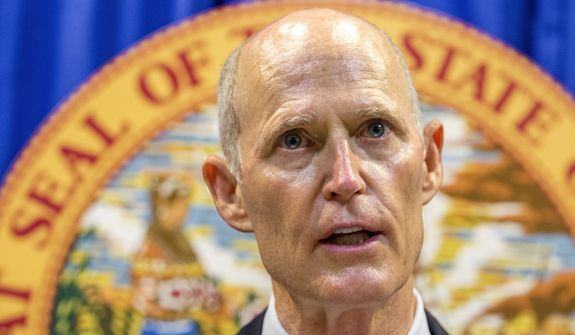 Florida Governor Rick Scott lays out his school safety proposal during a press conference at the Florida Capitol in Tallahassee, Fla., Friday, Feb 23, 2018. Scott proposed banning the sale of firearms to anyone younger than 21 as part of a plan to prevent gun violence. (AP Photo/Mark Wallheiser)