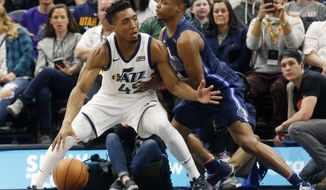 Utah Jazz's Donovan Mitchell (45) looks for an opening as Dallas Mavericks' Dennis Smith Jr., right, defends during the second half of an NBA basketball game Saturday, Feb. 24, 2018, in Salt Lake City. The Jazz won 97-90. (AP Photo/Kim Raff)