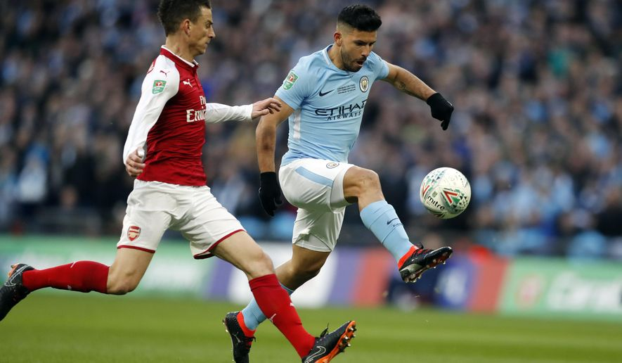 Manchester City's Sergio Aguero, right, scores the opening goal during the English League Cup final soccer match between Arsenal and Manchester City at Wembley stadium in London, Sunday, Feb. 25, 2018. (AP Photo/Frank Augstein)