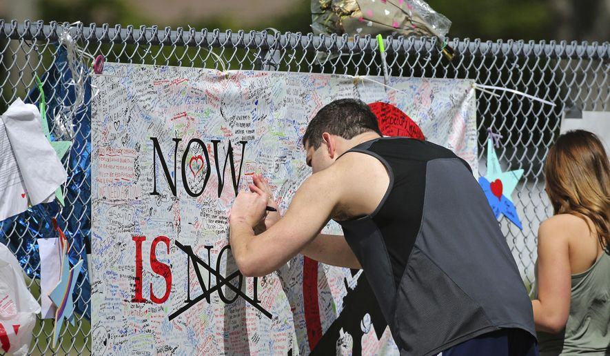 A man signs a banner as people pay tribute at a memorial for the victims of the shooting at Marjory Stoneman Douglas High School on Sunday, Feb. 25, 2018, in Parkland, Fla. Thousands of students joined their parents in walking past the three-story building at the Florida high school where the Feb. 14 shooting took place. It is now cordoned off by a chain link fence that was covered with banners from other schools showing their support. (David Santiago/Miami Herald via AP)