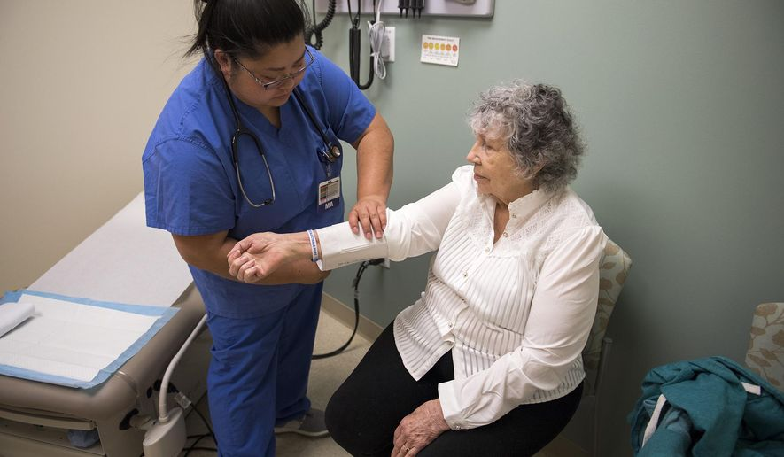 In this Feb. 13, 2018, photo, medical assistant Leena Amphornphong takes Phyllis Peterson's vitals during an appointment at Legacy Salmon Creek Medical Center in Vancouver, Wash. (Alisha Jucevic/The Columbian via AP)