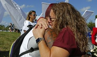 Pulse survivor India Godman, left, hugs Wendy Garrity at Marjory Stoneman Douglas High School in Parkland, Fla., Sunday, Feb. 25, 2018, for an open house as parents and students returned to the school for the first time since a shooting took place at the high school on Feb. 14. (David Santiago/Miami Herald via AP)