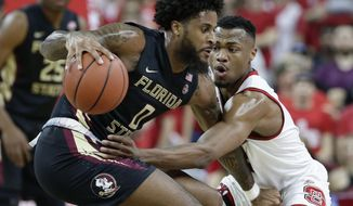 Florida State's Phil Cofer (0) dribbles while North Carolina State's Torin Dorn defends during the first half of an NCAA college basketball game in Raleigh, N.C., Sunday, Feb. 25, 2018. (AP Photo/Gerry Broome)