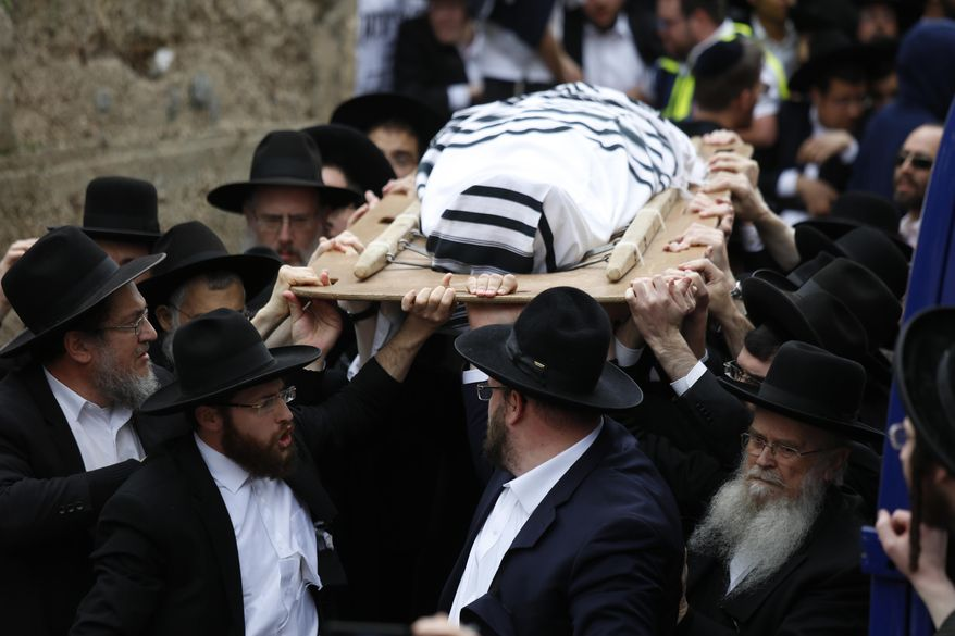 Ultra orthodox Jewish men carry the body of Rabbi Shmuel Auerbach during his funeral in Jerusalem, Sunday, Feb. 25, 2018. Tens of thousands of ultra-Orthodox Jews are attending the funeral of the influential rabbi who died on Saturday in Jerusalem. (AP Photo/Ariel Schalit)