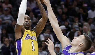 Los Angeles Lakers guard Kentavious Caldwell-Pope, left, shoots over Sacramento Kings guard Bogdan Bogdanovic during the first quarter of an NBA basketball game Saturday, Feb. 24, 2018, in Sacramento, Calif. (AP Photo/Rich Pedroncelli)