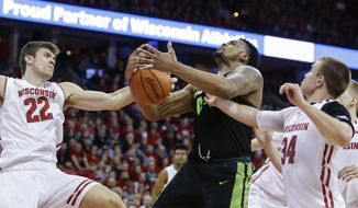 Michigan State's Nick Ward, center, battles for a rebound against Wisconsin's Ethan Happ, left, and Brad Davison, right, during the first half of an NCAA college basketball game Sunday, Feb. 25, 2018, in Madison, Wis. (AP Photo/Andy Manis)