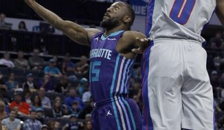 Charlotte Hornets' Kemba Walker (15) slips past Detroit Pistons' Andre Drummond (0) for an easy score during the first half of an NBA basketball game in Charlotte, N.C., Sunday, Feb. 25, 2018. (AP Photo/Bob Leverone)