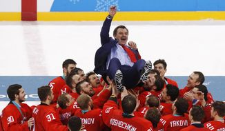 Olympic athletes from Russia celebrate with their coach Oleg Znarok after winning the men's gold medal hockey game against Germany, 4-3, in overtime at the 2018 Winter Olympics, Sunday, Feb. 25, 2018, in Gangneung, South Korea. (AP Photo/Jae C. Hong) **File**