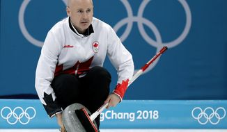 FILE - In this Feb. 23, 2018 file photo, Canada's skip Kevin Koe uses his broom to clean the stone during the men's curling match against Switzerland at the 2018 Winter Olympics in Gangneung, South Korea. Koe, works full time as a surface landman for an oil and gas company, liaising with landowners and farmers. He often finds himself working even while on the road for curling competitions, making calls and answering emails in between matches so he can stay on top of things.  (AP Photo/Aaron Favila, File)