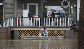 A man paddles his boat alongside a home in the East End along the Ohio River, Saturday, Feb. 24, 2018 in Cincinnati.  Forecasters expected the Ohio River could reach levels not seen since the region's deadly 1997 floods.(Liz Dufour/The Cincinnati Enquirer via AP)