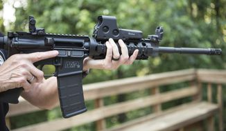 FILE - In this June 24, 2016 file photo, an AR-15 is held in Auburn, Ga.   Gun rights advocates entered the Trump era with high hopes. After years of frustration they thought a gun-friendly president and Congress would advance their agenda.  (AP Photo/Lisa Marie Pane)
