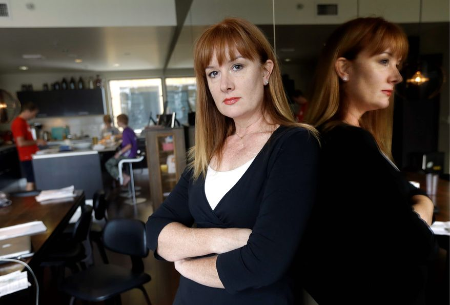 Kim Sordyl poses for a photo at home as her family eats breakfast in the kitchen in Portland, Ore., on Friday, July 7, 2017. In April 2017, the Portland, Ore., school district filed a lawsuit against Sordyl, who is seeking records about employees on leave for alleged misconduct after the disclosure that one psychologist had been off for three years. Sordyl said she believes the information will expose costly missteps by district human resources officials and lawyers, and the district attorney has already ordered the records to be released. (AP Photo/Don Ryan)