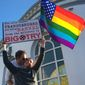 Nick Rondoletto, left, and Doug Thorogood, a couple from San Francisco, wave a rainbow flag and hold a sign against a proposed ban of transgendered people in the military at a protest in the Castro District, Wednesday, July 26, 2017, in San Francisco. Demonstrators flocked to a plaza named for San Francisco gay-rights icon Harvey Milk to protest President Donald Trumps abrupt ban on transgender troops in the military. (AP Photo/Olga R. Rodriguez)