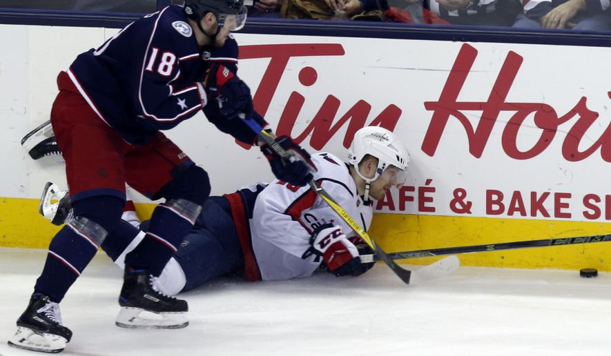 Washington Capitals forward Lars Eller, right, of Denmark, reaches for the puck against Columbus Blue Jackets forward Pierre-Luc Dubois during the third period of an NHL hockey game in Columbus, Ohio, Monday, Feb. 26, 2018. The Blue Jackets won 5-1. (AP Photo/Paul Vernon)
