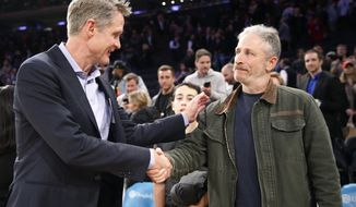 Golden State Warriors head coach Steve Kerr, left, greets former TV show host Jon Stewart on during the second half of an NBA basketball game, Monday, Feb. 26, 2018 in New York. The Warriors defeated the Knicks 125-111. (AP Photo/Kathy Willens) **File**