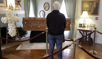 A man pauses by the casket as he pays respects to Billy Graham during a public viewing at the Billy Graham Library in Charlotte, N.C., Monday, Feb. 26, 2018. (AP Photo/Chuck Burton)