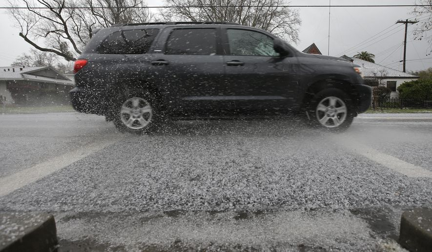 A car sends hail stones flying as it drives through a sudden hail storm that passed through the area Monday, Feb. 26, 2018, in Sacramento, Calif. (AP Photo/Rich Pedroncelli)