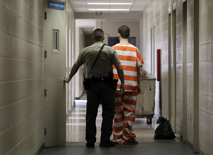 FILE - In this Feb. 21, 2013, file photo, an inmate at the Madera County, Calif., Jail is taken to an inmate housing unit in Madera, Calif. The California Supreme Court is set to decide Monday, Feb. 26, 2018, the constitutionality of criminal sentences that don't give juveniles an opportunity for parole for 50 years or more. (AP Photo/Rich Pedroncelli, File)