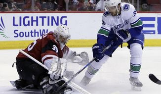 Arizona Coyotes goaltender Darcy Kuemper (35) makes the save on Vancouver Canucks center Brandon Sutter in the first period during an NHL hockey game, Sunday, Feb. 25, 2018, in Glendale, Ariz. (AP Photo/Rick Scuteri)