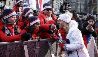 Two time gold winter olympic medalist Ester Ledecka greets her fans at the Old Town Square in Prague, Czech Republic, Monday, Feb. 26, 2018. Ester Ledecka has received a hero's welcome in the Czech capital after winning an unprecedented double at the 2018 Winter Olympics in Pyeongchang, taking the gold medal in snowboarding's parallel giant slalom to pair with her shocking skiing victory in the Alpine super-G. (AP Photo/Petr David Josek)
